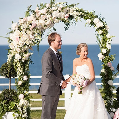Bride and Groom standing in front of beautiful flowers at an outdoor wedding.