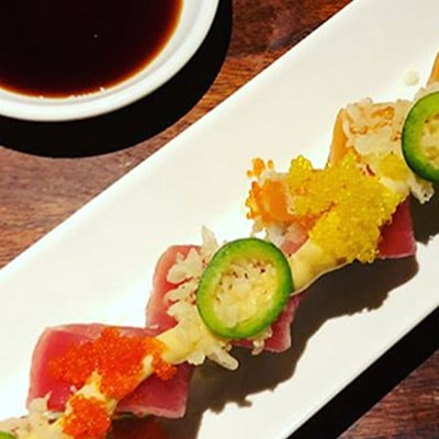 elegantly plated sushi selection with bowl of dipping sauce from Inaho