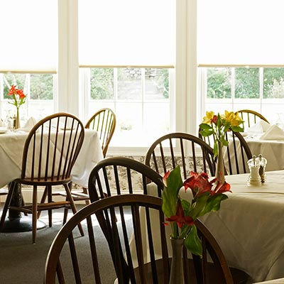 Interior of Old Yarmouth Inn Dining room, colonial chairs, fresh flowers, large windows & sunlight